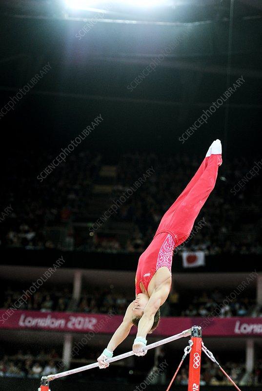 Gymnast on high bar, London 2012 - Stock Image - C015/5900