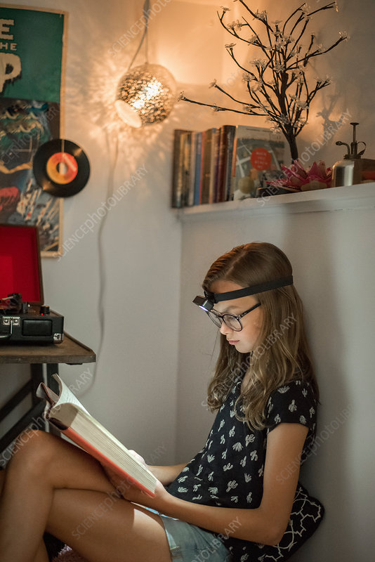 A Girl Reading A Book In A Quiet Corner Using A Head Torch Stock