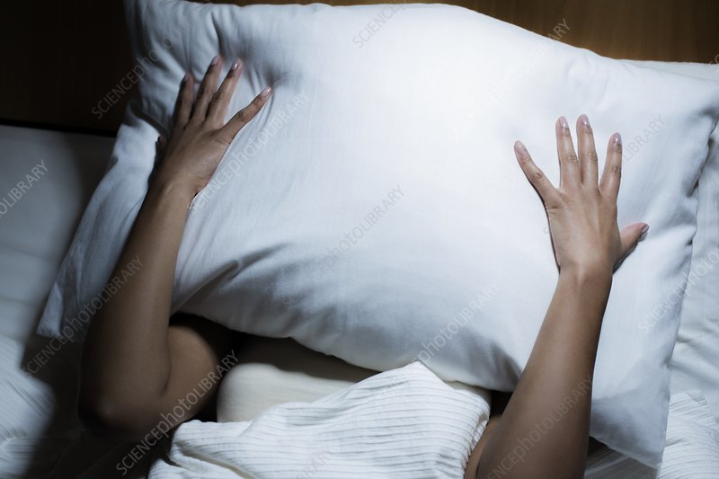 Woman covering her face with pillow - Stock Image - F026/5385 - Science  Photo Library