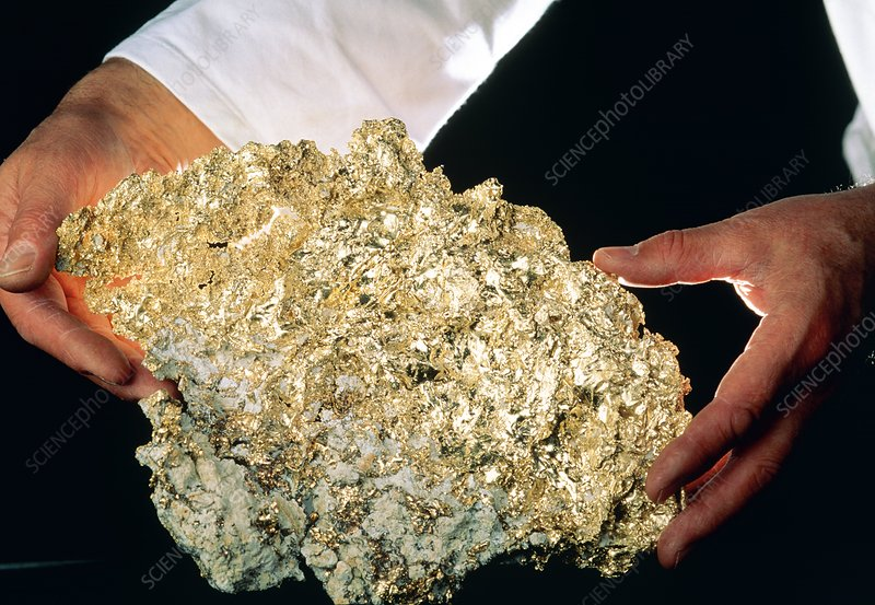 Hands holding rock containing native gold