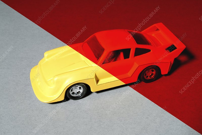 Yellow toy car under red light