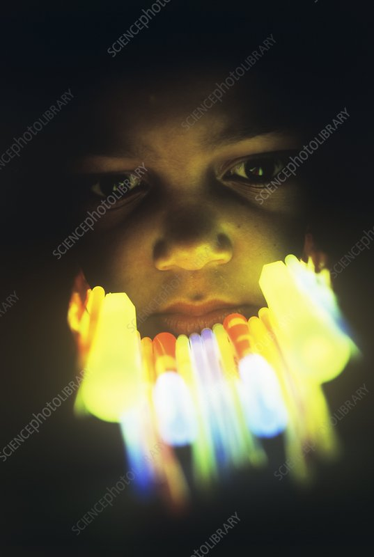 Boy's face lit by glow sticks