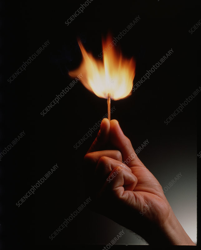 Hand holds a match ignited