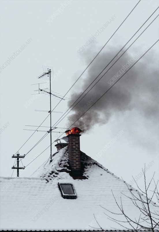 Burning chimney on snowy house