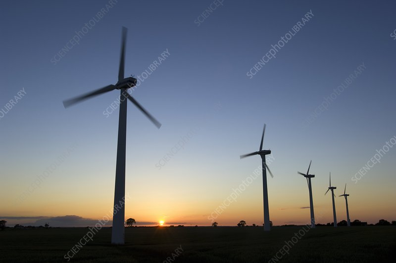 Row of wind turbines at sunset