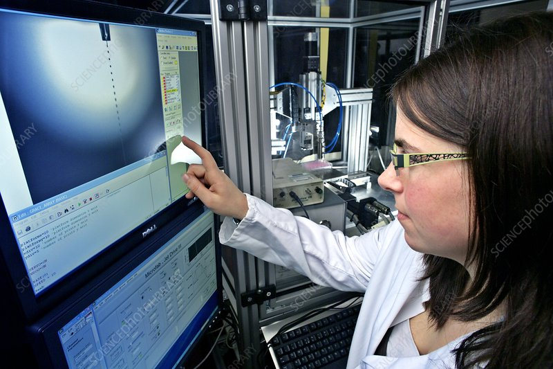 Researcher examining bioprinter on screen