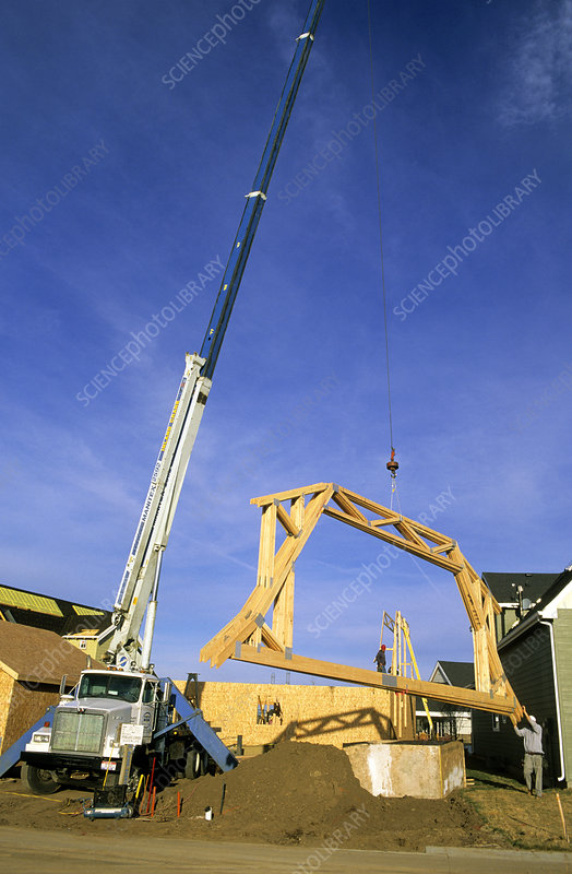 Crane delivering truss