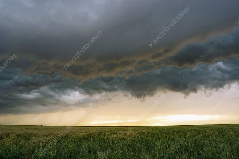 Stormy sky over fields at sunset