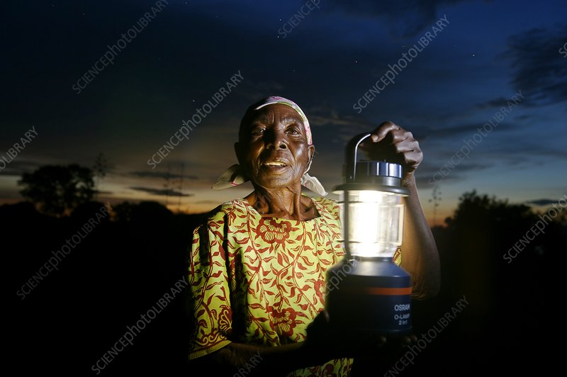 Woman holding a solar powered lamp, Kenya