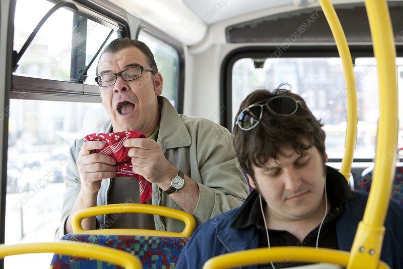 Man sneezing on public transport