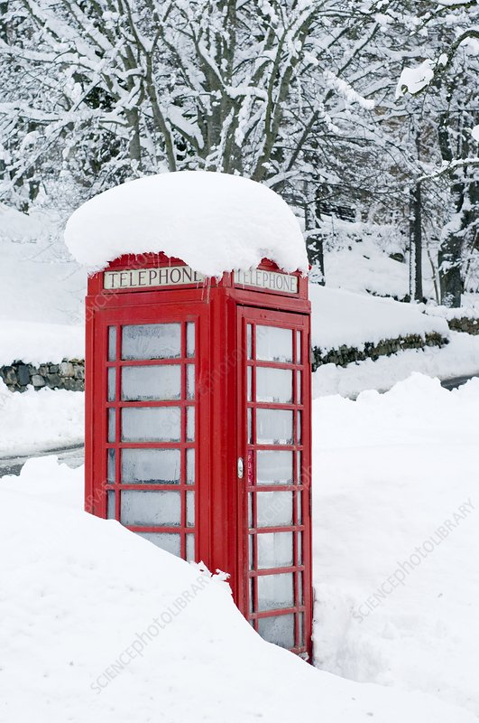 Red telephone box in heavy snow