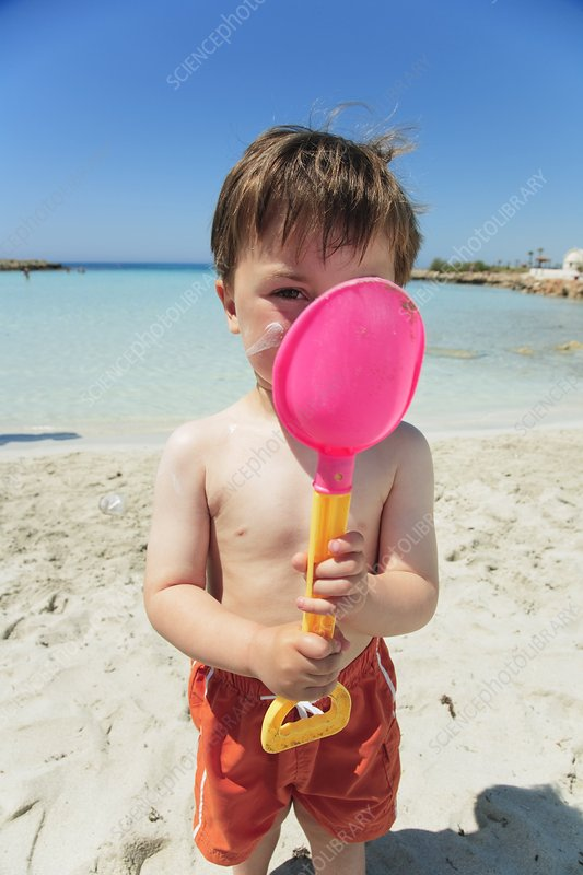 Boy holding spade with sun lotion on face