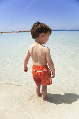 Boy testing the sea temperature with feet