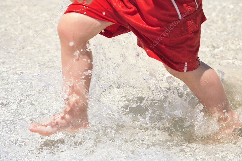 Boy running through sea water at beach