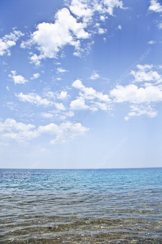 Blue sky, fluffy clouds and clear sea