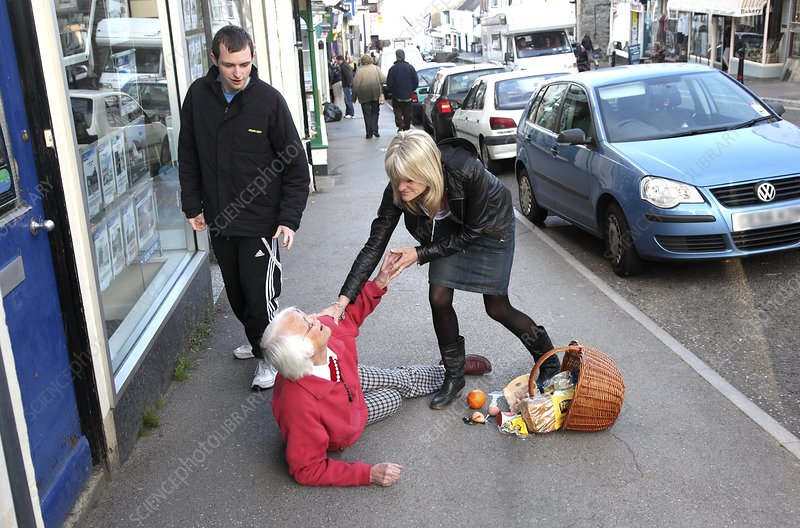 Elderly woman being helped after falling