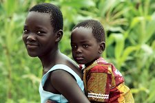 Girl carrying a young child, Uganda