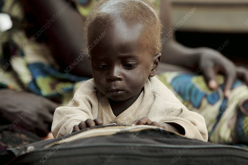 Baby playing with a book, Uganda