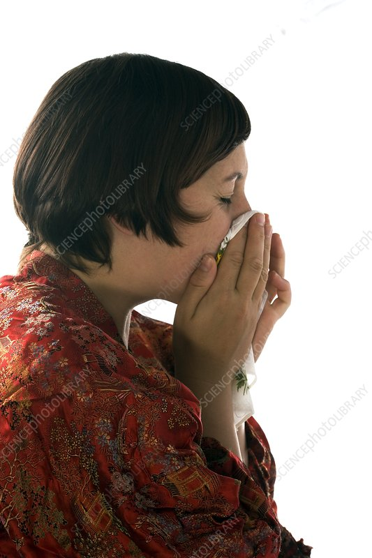 Woman sneezing into a handkerchief