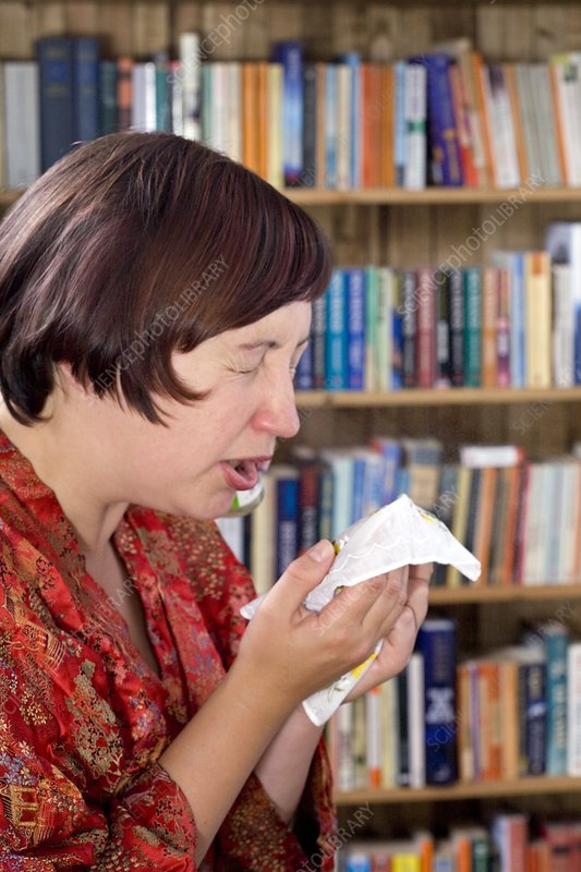 Woman sneezing into a handkerchief