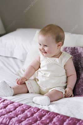 Baby girl sitting on a bed