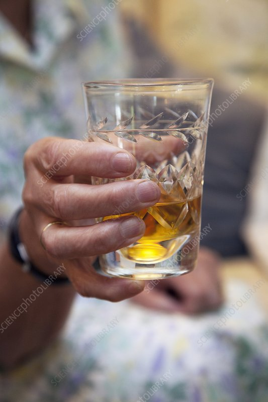 Glass of sherry in elderly woman's hand