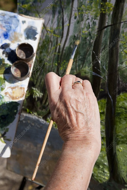 Hand of an elderly woman painting