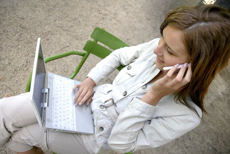 Woman using a laptop and mobile phone