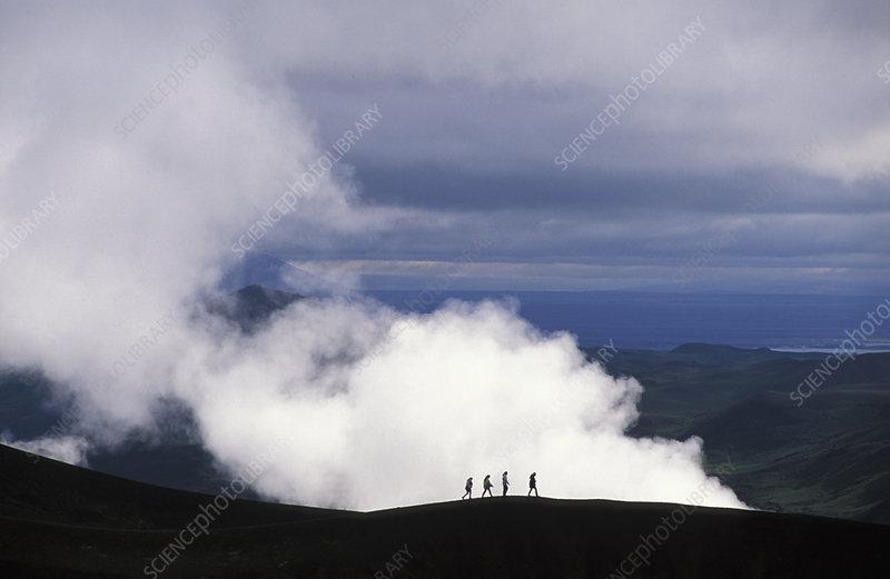 Hikers walk along the rim of Viti Crater
