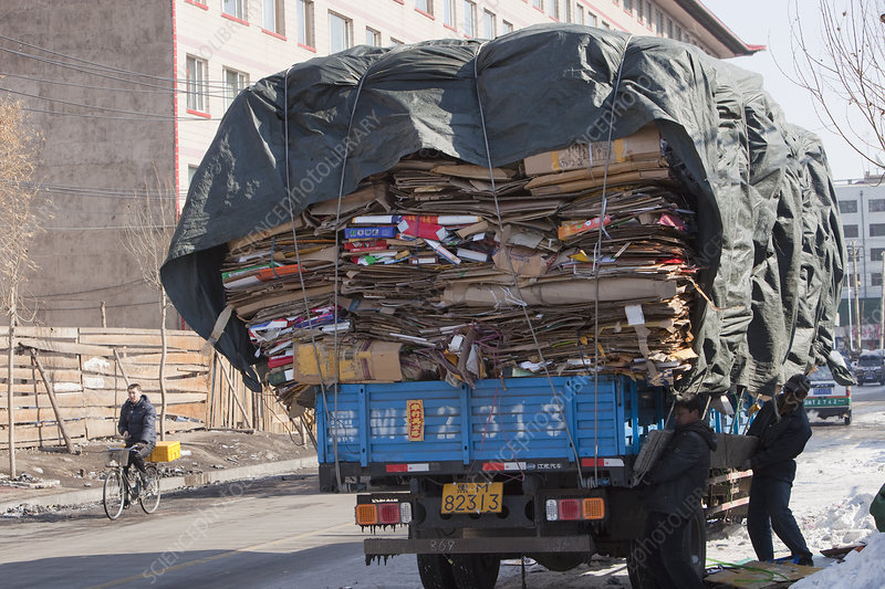 Workers loading a truck with cardboard
