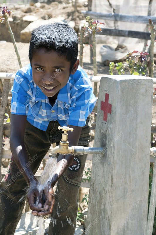 Boy playing with water, Timor-Leste