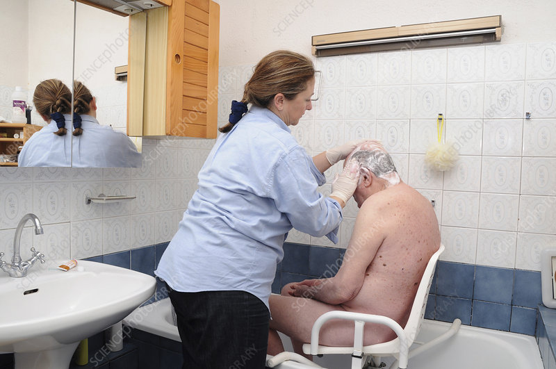 Nurse washing elderly person