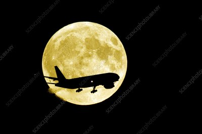 Aeroplane silhouetted against a full moon