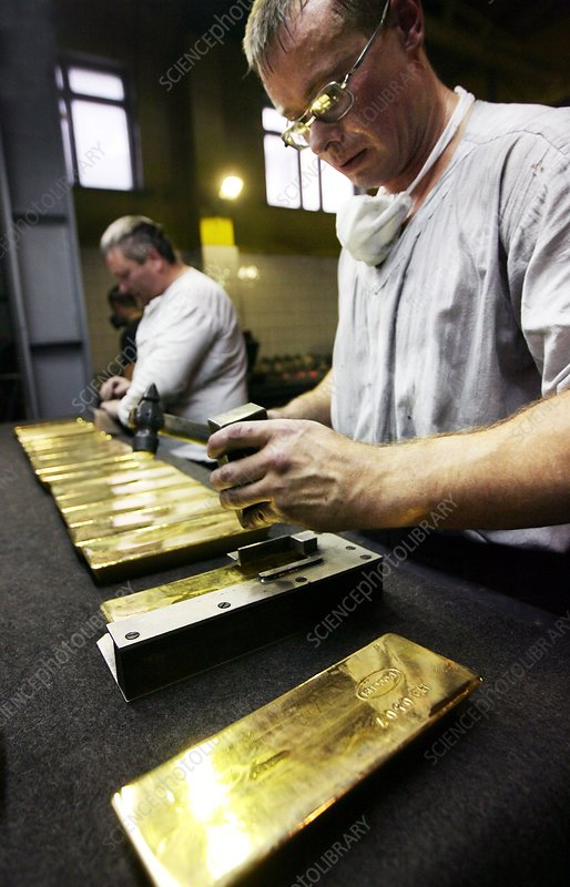Worker stamping gold bars