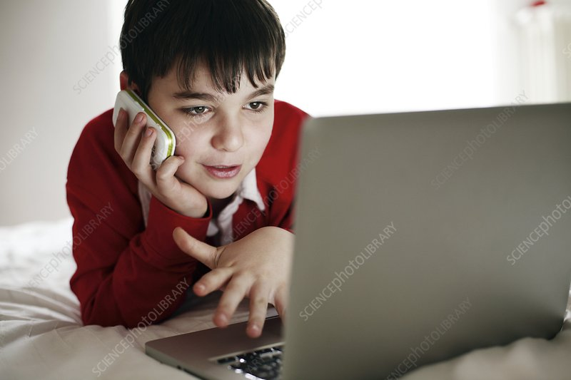 Boy using a mobile phone and laptop