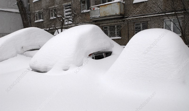 Snow-covered cars in a city