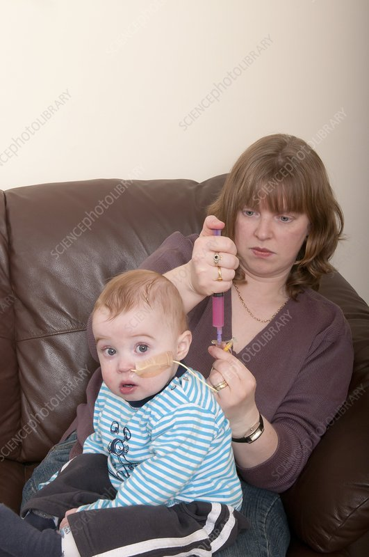 Mother medicating child with NG tube