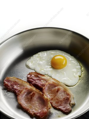 Bacon and eggs cooking in a frying pan