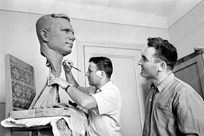 Yuri Gagarin autographing his portrait