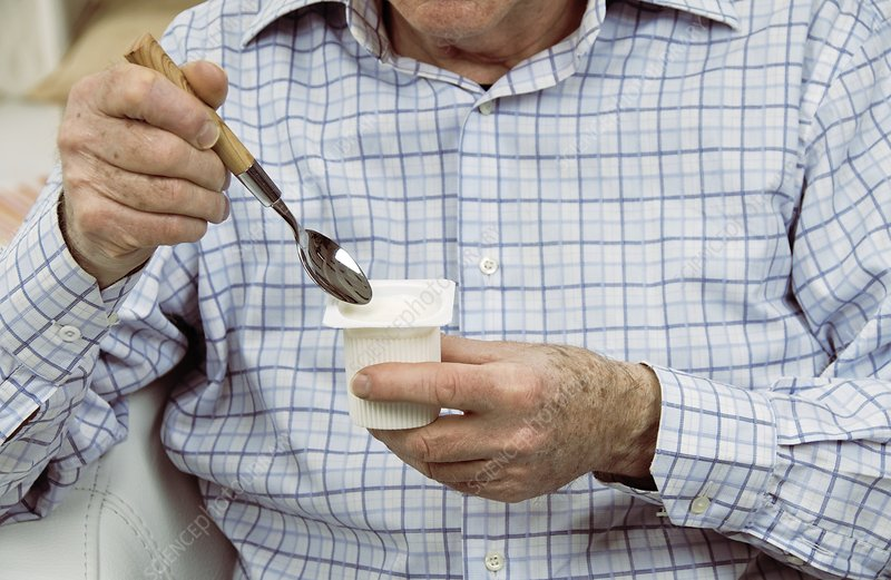 Elderly man eating a yoghurt