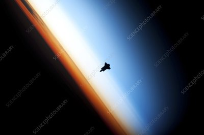 Space shuttle over Earth's horizon