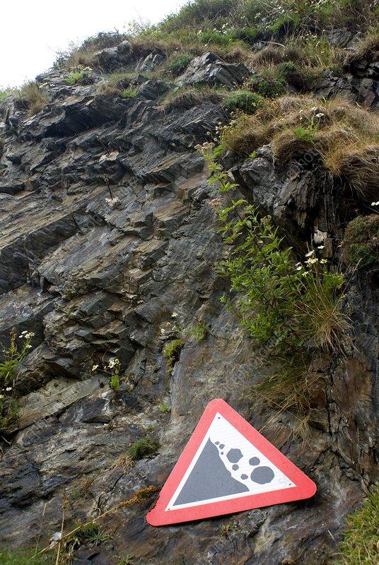 Falling rocks warning sign on cliffs