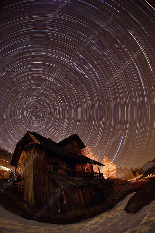 Star trails over an Alpine cottage
