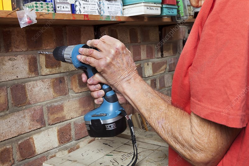 Elderly man using an electric drill