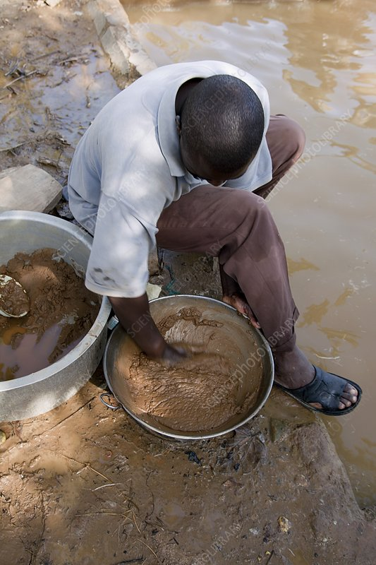 Artisan miner panning for gold, Kenya