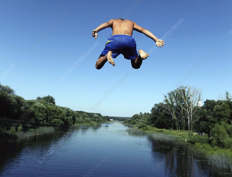 Boy jumping into a river