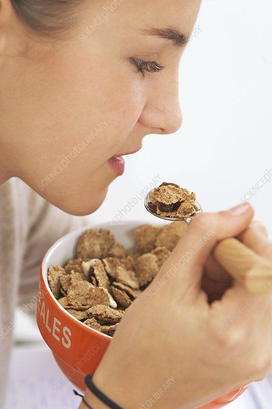 Teenage girl eating cereal