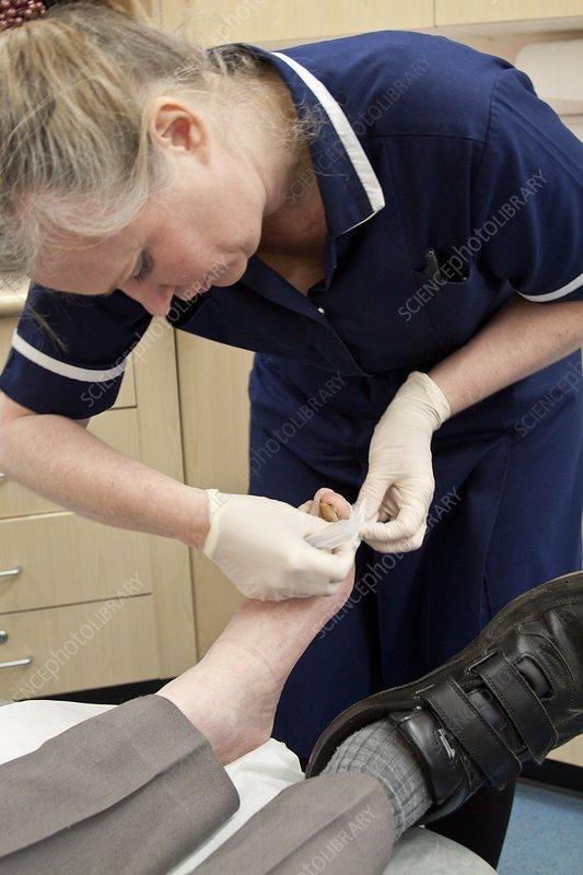 Nurse dressing a patient's toe