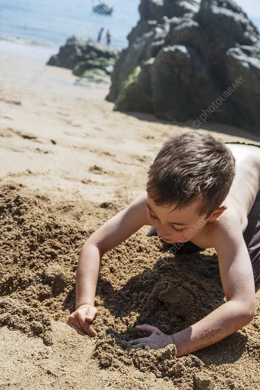 Boy playing in sand at the beach