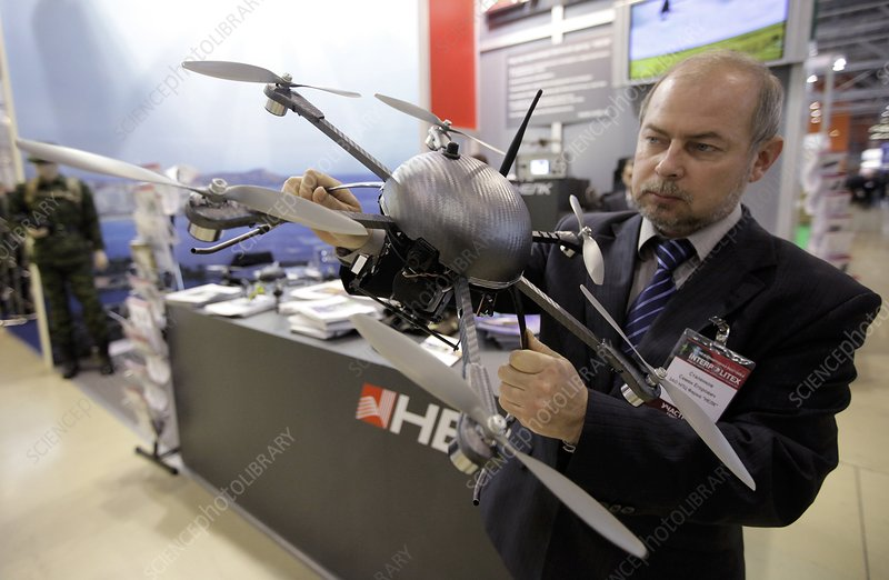 Man holding small UAV flying machine